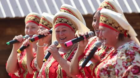 kalmak : REPUBLIC OF TATARSTAN, RUSSIA: 04.07.2019 - Women in traditional tatar clothes stay in a row and singing with the microphone