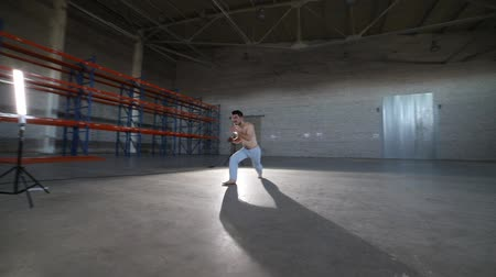akrobata : A man doing different capoeira elements in the room with concrete floor, brick walls and bright light