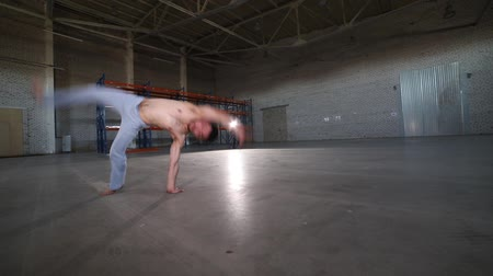 akrobata : A man doing different capoeira elements - staying on his hand and doing a cartwheel - in the room with concrete floor, brick walls and bright light