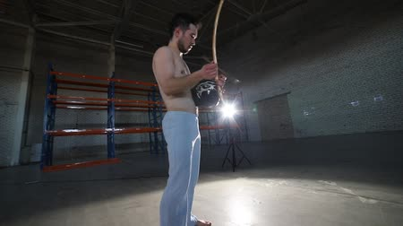 traditional instruments : An athletic man playing on national brazilian instrument berimbau after doing capoeira elements in the room with concrete floor and brick walls
