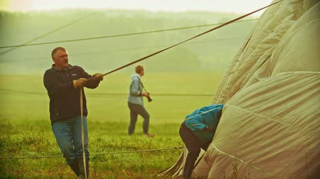 vzducholoď : 18-07-2019 Pereslavl-Zalessky, Russia: people preparing air balloons for flying. Men holding the ropes Dostupné videozáznamy