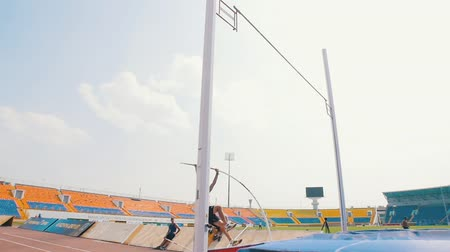 mais alto : KAZAN, RUSSIA 26-07-2019: a shirtless man running up and leans on a pole to jump over the bar - unsuccessful attempt