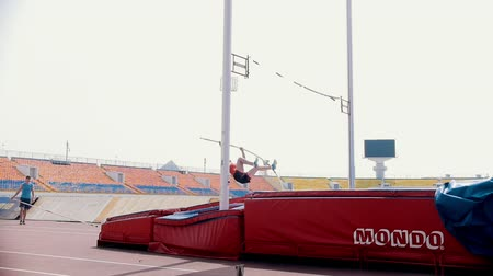alcançando : KAZAN, RUSSIA 26-07-2019: a woman running up and leans on a pole to jump over the bar - unsuccessful attempt because of touching the bar - pole vault training