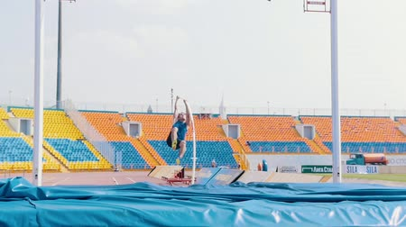 realizar : KAZAN, RUSSIA 26-07-2019: a young man in blue shirt running up and leans on a pole to jump over the bar - pole vault training on stadium - unsuccessful attempt because of touching the bar Vídeos