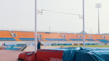 suceder : KAZAN, RUSSIA 26-07-2019: an athletic man in blue shirt running up and leans on a pole to jump over the bar - pole vault training on stadium Vídeos