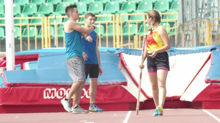 realizar : KAZAN, RUSSIA 26-07-2019: three athletic people on pole vault training in stadium - talking and laughing. Mid shot Vídeos