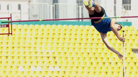 ugró : KAZAN, RUSSIA 26-07-2019: a young athletic man jumping over the bar with an effort - pole vault training on stadium