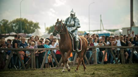 ライバル : BULGAR, RUSSIA 11-08-2019: A man knight riding a horse near the fence while the fight tournament