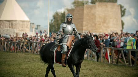gladiador : BULGAR, RUSSIA 11-08-2019: A man knight with opened helmet riding a horse around the battlefield - people watching behind the fence