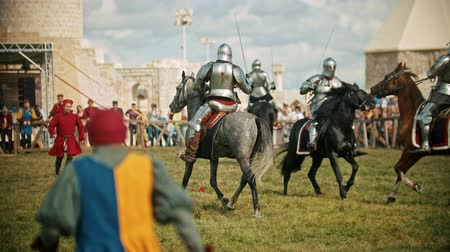 beygir gücü : BULGAR, RUSSIA 11-08-2019: Knights with swords riding horses on the battlefield and crossing their swords - people watching behind the fence - medieval festival Stok Video