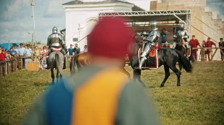 knightly : BULGAR, RUSSIA 11-08-2019: Knights with swords riding horses on the battlefield and having a training battle - people watching behind the fence - medieval festival Stock Footage