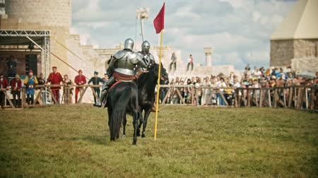 knightly : BULGAR, RUSSIA 11-08-2019: Knights with swords riding horses on the battlefield and having a training battle - people watching behind the fence