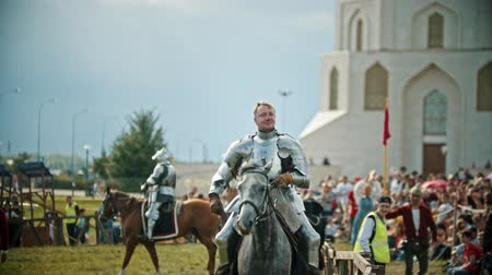 knightly : BULGAR, RUSSIA 11-08-2019: A man knight riding a horse around the battlefield and greeting the people watching behind the fence Stock Footage