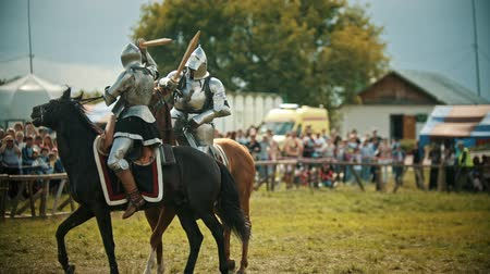 knightly : BULGAR, RUSSIA 11-08-2019: Knights having a battle on wooden swords on the field - people watching behind the fence - medieval festival