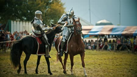 rytíř : BULGAR, RUSSIA 11-08-2019: Knights in metal armor having a battle on wooden swords on the field - people watching behind the fence - medieval festival