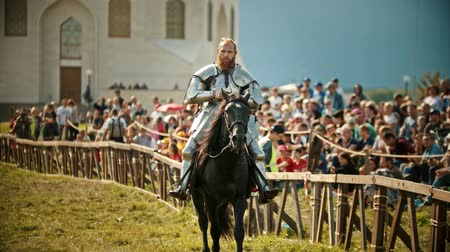 adversidade : BULGAR, RUSSIA 11-08-2019: A bearded man knight riding a horse near the fence while the fight tournament