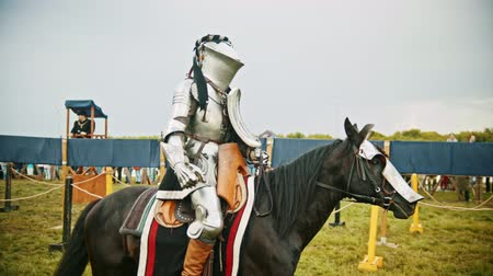 zbroja : BULGAR, RUSSIA 11-08-2019: Knight with a massive helmet riding a black horse on the field Wideo