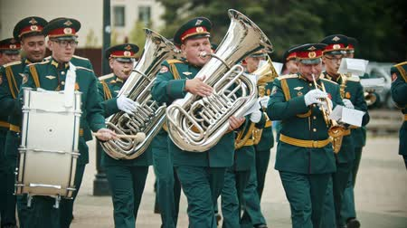 trombeta : RUSSIA, KAZAN 09-08-2019: A wind instrument parade - military musicians in green costumes walking on the street holding musical instruments Stock Footage