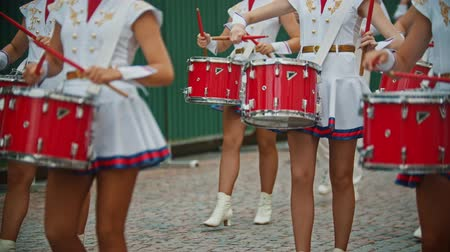 медь : RUSSIA, KAZAN 09-08-2019: A wind instrument military parade - women with bright make up in small skirts playing red drums