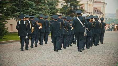 медь : RUSSIA, KAZAN 09-08-2019: A wind instrument parade - military musicians in black costumes marching on the street holding musical instruments Стоковые видеозаписи