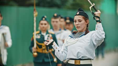 медь : RUSSIA, KAZAN 09-08-2019: A wind instrument military parade - woman showing tricks with swords