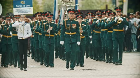 szakszofon : RUSSIA, KAZAN 09-08-2019: A wind instrument parade - military musicians in green costumes marching on the street holding musical instruments - a man holding a nameplate says Rostov-on-Don Orchestra