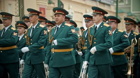 trąbka : RUSSIA, KAZAN 09-08-2019: A wind instrument parade - military musicians in green costumes marching on the street holding musical instruments