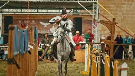 zbroja : BULGAR, RUSSIA 11-08-2019: Knight riding through the path and takes the ring from the fence using a spear