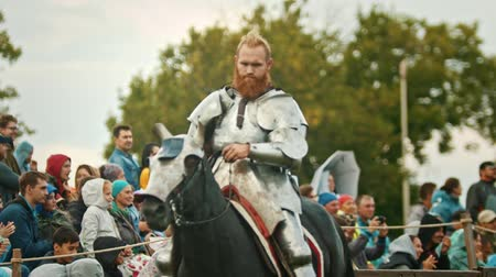 knightly : BULGAR, RUSSIA 11-08-2019: Knight riding a horse around the field - people watching him