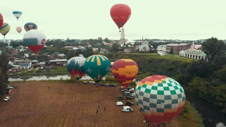 ascenso : 18-07-2019 Suzdal, Russia: different colorful air balloons are flying over the village - different inscriptions of brands on the balloons