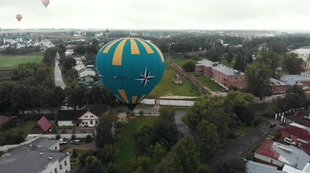 ascenso : 18-07-2019 Suzdal, Russia: different huge air balloons are flying over the village - different inscriptions of brands written on the balloons Archivo de Video