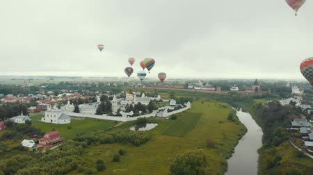 ascension : 18-07-2019 Suzdal, Russia: different huge colorful air balloons are flying over the village - different inscriptions of brands on the balloons
