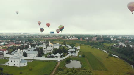 오르막 : 18-07-2019 Suzdal, Russia: different huge colorful air balloons are flying over the village and fields - different inscriptions of brands on the balloons