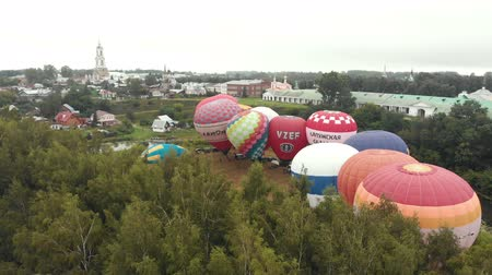 오르막 : 18-07-2019 Suzdal, Russia: different colorful air balloons are preparing to take off over the field - different inscriptions on the balloons - forest and village around