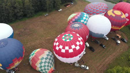 being prepared : 18-07-2019 Suzdal, Russia: different colorful air balloons being prepared to take off over the field - different inscriptions on the balloons - forest and village around