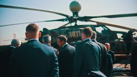 экспозиция : 30 AUGUST 2019 MOSCOW, RUSSIA: an outdoors airplane exposition - businessmen in suits standing by the helicopter