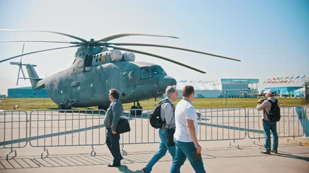 экспозиция : 30 AUGUST 2019 MOSCOW, RUSSIA: an outdoors airplane exposition - people walking by the helicopter Стоковые видеозаписи