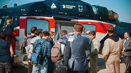 aircraft cabin : 30 AUGUST 2019 MOSCOW, RUSSIA: An outdoors aircraft exhibition - people standing by the helicopter and listening the guide lecture Stock Footage