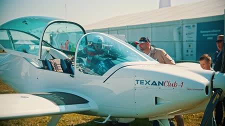 guerra : 30 AUGUST 2019 MOSCOW, RUSSIA: An outdoors aircraft exhibition - a seaplane TEXANClub-1 - a kid sitting down in the pilot cabin Stock Footage