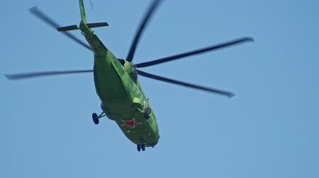 fly away : 29 AUGUST 2019 MOSCOW, RUSSIA: A military bright green helicopter with red star on the the bottom flying away in the sky