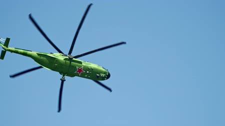 sierpien : 29 AUGUST 2019 MOSCOW, RUSSIA: An army bright green camouflage helicopter with red stars on the corpus at the bottom flying in the sky Wideo