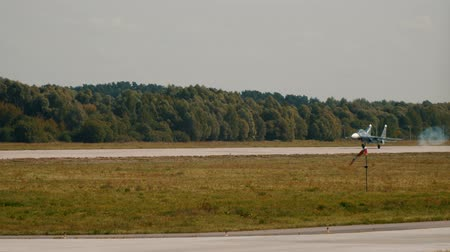 futópálya : 30 AUGUST 2019 MOSCOW, RUSSIA: Russian Air Force - grey reactive fighter jet landing and slows down on the runway - hot air around