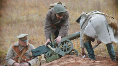 rytíř : RUSSIA, REPUBLIC OF TATARSTAN 30-09-2019: A reconstruction of military operations in Russia in 1917 - A military man fixing the position of a machine gun and another soldiers watching him