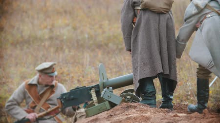 historical reconstruction : RUSSIA, REPUBLIC OF TATARSTAN 30-09-2019: A reconstruction of military operations in Russia in 1917 - Soldiers putting a machine gun in the right place on the ground Stock Footage