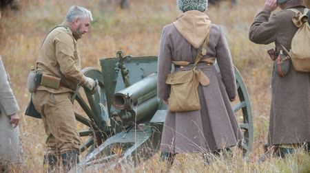 historical reconstruction : RUSSIA, REPUBLIC OF TATARSTAN 30-09-2019: A reconstruction of military operations in Russia in 1917 - Soldiers setting the cannon gun in place on the battlefield