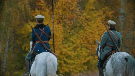 historical reconstruction : RUSSIA, REPUBLIC OF TATARSTAN 30-09-2019: A reconstruction of military operations in Russia in 1917 - Two military men riding horses towards the autumn forest Stock Footage