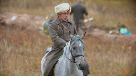rytíř : RUSSIA, KAZAN 30-09-2019: A man soldier riding on the back of the white horse on the field wearing a warm hat Dostupné videozáznamy