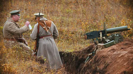 броня : RUSSIA, KAZAN 30-09-2019: A reconstruction of military operations in Russia in 1917 - Soldiers standing in the trench and drinking water from the bottle Стоковые видеозаписи