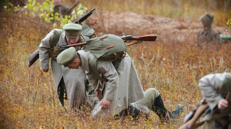 historical reconstruction : RUSSIA, REPUBLIC OF TATARSTAN 30-09-2019: A reconstruction of military operations in Russia in 1917 - Performing hostilities - Soldiers drag their comrade away from the battlefield