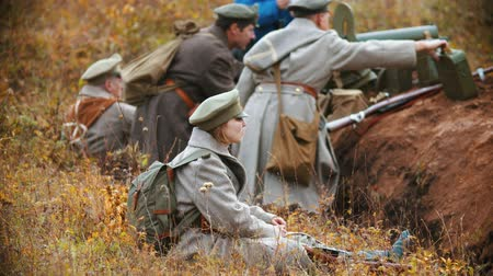 historical reconstruction : RUSSIA, REPUBLIC OF TATARSTAN 30-09-2019: A reconstruction of military operations in Russia in 1917 - Performing hostilities - A woman soldier sitting on the field Stock Footage